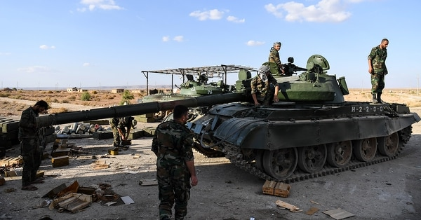 Members of the Syrian pro-regime forces ride atop a tank prior to advancing towards rebel-held positions west of Aleppo in November 2017. (George Ourfalian/AFP/Getty Images)