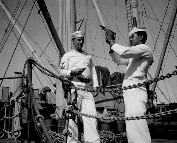 Coxswain William Green observes safety precautions in checking his pistol while Albert S. Herbert, quartermaster first class, stands by ammunition and holster belt, ready to complete the formalities. (National Archives)