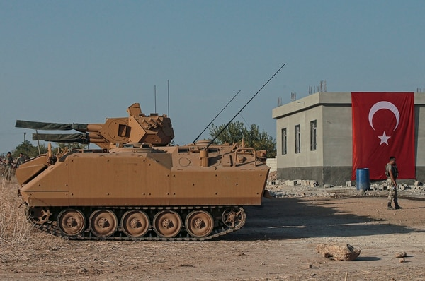 Turkish army personnel carriers are parked on a road towards the border of Syria in Sanliurfa province, Turkey, Monday, Oct. 14, 2019. (Emrah Gurel/AP)