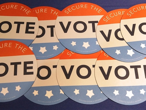 In this July 14, 2018, file photo, computer mouse pads with Secure the Vote logo on them are seen on a vendor's table at a convention of state secretaries of state in Philadelphia. (Mel Evans/AP)