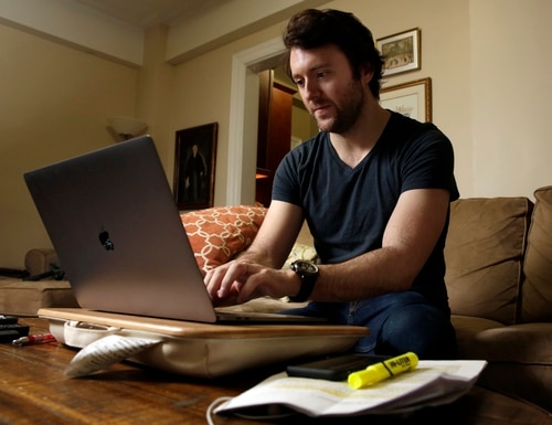 Journalist Michael Weiss works on his laptop in his apartment on New York's Upper West Side, Friday, Dec. 8, 2017. (Richard Drew/AP)