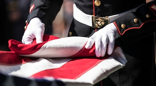A U.S. Marine folds the American flag during the funeral of a Marine in 2019. (Cpl. Tessa D. Watts/Marine Corps)