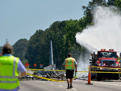 A firetruck sprays foam over the remains of an Air National Guard C-130 cargo plane from Puerto Rico that crashed in Port Wentworth, Ga., near Savannah, May 2. Nine airmen from the Puerto Rico Air National Guard died in the accident; no one was injured on the ground. (Steve Bisson/Savannah Morning News via AP)