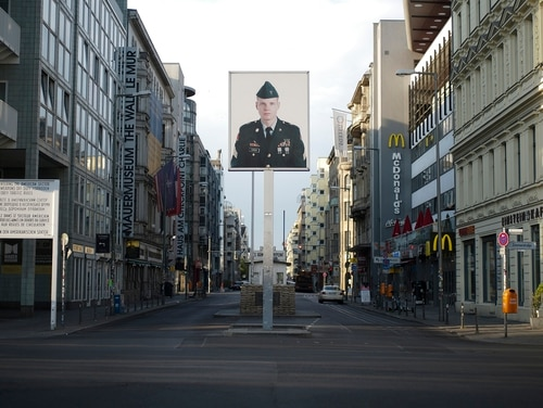 In this June 9, 2020, file photo, a picture of a former American soldier is displayed at the former U.S. Army Checkpoint Charlie in Berlin, Germany. (Markus Schreiber/AP)