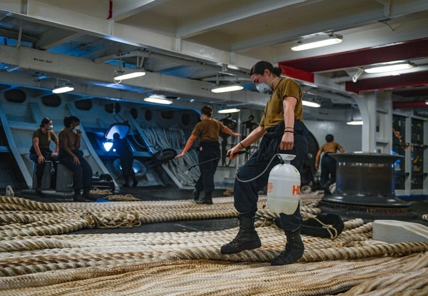 Boatswain's Mate Seaman Alexis Bias, assigned to the aircraft carrier Theodore Roosevelt, disinfects the mooring line on May 21, 2020, following an extended visit to Guam in the midst of the COVID-19 pandemic. (MC3 Conner D. Blake/U.S. Navy)