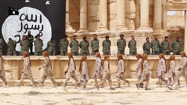 An image grab taken from a video made available by Jihadist media outlet Welayat Homs on July 4, 2015 allegedly shows 25 Syrian government soldiers kneeling as, what appears to be children or teenagers, wearing desert camouflage walk beneath them in the ancient amphitheatre in the city of Palmyra. The executions in the Palmyra amphitheatre were first reported on May 27 by the Syrian Observatory for Human Rights, a Britain-based monitor, less than a week after IS captured the city. AFP PHOTO / HO / WELAYAT HOMS=== RESTRICTED TO EDITORIAL USE - MANDATORY CREDIT