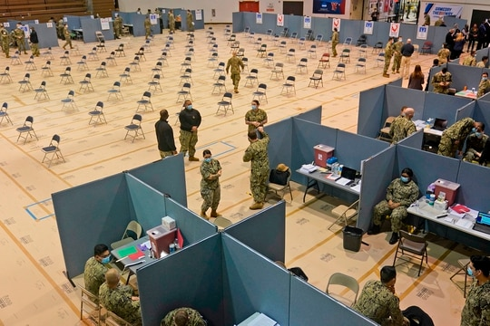 Military personnel prepare for the opening of a mass Covid-19 vaccination site in the Queens borough of New York on Feb. 24, 2021. (Seth Wenig/AFP via Getty Images)