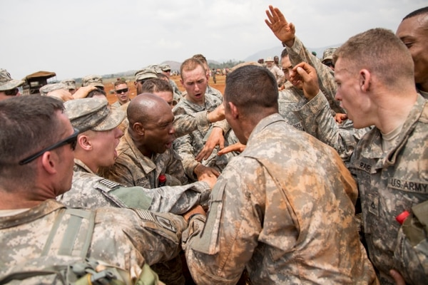 U.S. Army paratroopers with Chosin Company, 2nd Battalion, 503rd Infantry Regiment, 173rd Infantry Brigade Combat Team (Airborne), bring it in for a cheer after conducting airborne operations during Central Accord 2014 (CA 14) in Cameroon, Africa, March 17, 2014. CA 14 is a culmination of Military Forces of Central Africa, the Netherlands, and the United States conducting a combined joint training exercise in order to sustain tactical proficiency, improve multi-echelon operations, and develop multi-national logistical capabilities in an austere forward environment. (U.S. Army photo by Staff Sgt. Kaily Brown/ Released)