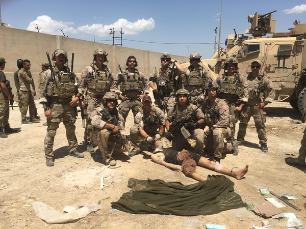 Members of Alpha Platoon, SEAL Team 7, pose in front of the body of a dead Islamic State prisoner of war in Iraq in 2017. Only Gallagher was convicted for appearing in the image. (Navy)