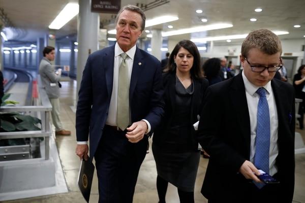 Senator David Perdue (R-GA) berjalan bersama para pembantunya di Capitol Hill pada 14 Februari 2018 di Washington, DC. (Foto oleh Aaron P. Bernstein / Getty Images)