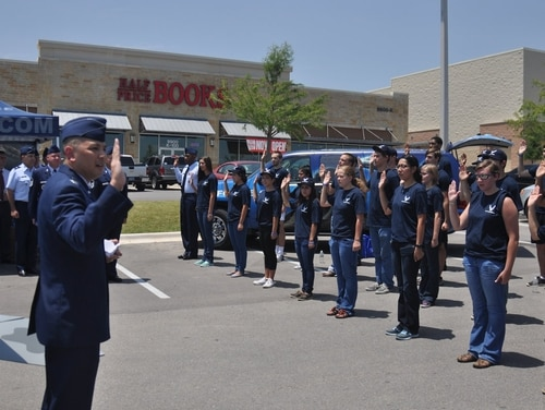 A recent enlistee in the Air Force Reserve may be kicked out after a video showing her making a racial slur went viral. In this photo, Col. Robert Borja, 369th Recruiting Group commander, administers the oath of enlistment to more than 60 Delayed Entry Program members in Austin, Texas, Aug. 1, 2013. (Staff Sgt. Hillary Stonemetz/Air Force)