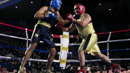 Charles Patterson, left, from Honolulu, HI lands a punch to the jaw of Joey Resendez, right, from El Paso, TX, in the Heavyweight fight during the United States Naval Academy's 77th Brigade Boxing Championships held on Feb. 23, 2018. Patterson won the fight. (Alan Lessig/Staff)