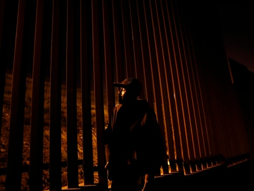 An immigrant from Nicaragua stands on the Mexico side of a border wall separating Tijuana from the United States on Jan. 9, 2019. A new House bill would extend citizenship privileges to immigrants who served in the U.S. military but were later convicted of a crime, making them vulnerable to deportation. (Gregory Bull/AP)