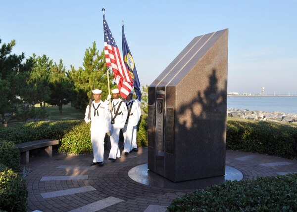 Members of a Navy honor guard from the guided-missile destroyer USS Cole practice rendering colors before a memorial service at the USS Cole Memorial at Naval Station Norfolk. The Norfolk-based ship was damaged by a suicide bombing while refueling in the Port of Aden in Yemen, killing 17 and wounding 39 Sailors. Cole returned to the fleet in 2002 and has deployed four times since the attack.