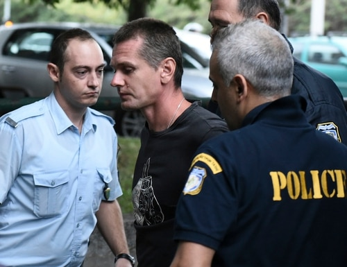 A Russian man identified as Alexander Vinnik, center, is escorted by police officers to the courthouse at the northern Greek city of Thessaloniki on Friday, Sept. 29, 2017. (AP Photo/Giannis Papanikos)