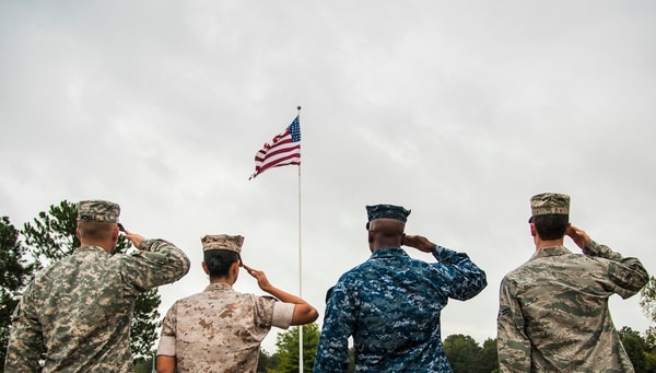 Service members salute the American flag during a retreat ceremony Oct. 2, 2014, at Little Rock Air Force Base, Ark. (Airman 1st Class Harry Brexel/Air Force)