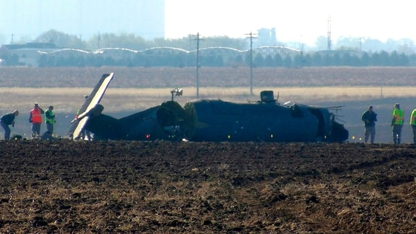 This frame grab from video supplied by KFDA-TV shows investigators looking over the broken fuselage of an Air Force plane March 15, 2017, in Clovis, N.M. The Air Force says three service members were killed when the single-engine reconnaissance and surveillance plane crashed in eastern New Mexico during a training flight. (KFDA-TV via AP)