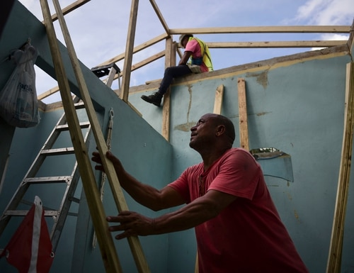 In this Nov. 15, 2017 photo, Pedro Deschamps helps workers hired by FEMA to carry out the installation of a temporary awning roof at his house, which suffered damage during Hurricane Maria, in San Juan, Puerto Rico. (Carlos Giusti/AP)