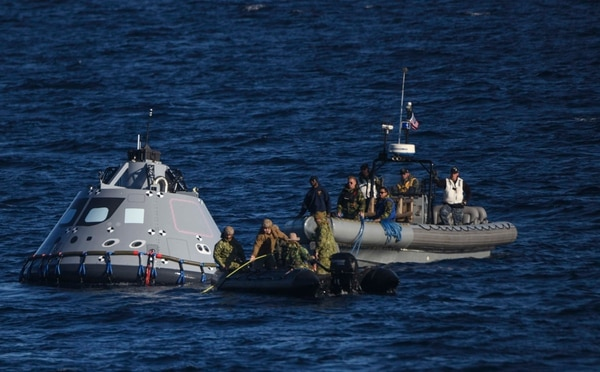 Sailors in a Rigid Hull Inflatable Boat assist divers in Combat Rubber Raiding Craft (CRRC) from Explosive Ordnance Disposal Mobile Unit 3. (MC3 Natalie M. Byers/Navy)