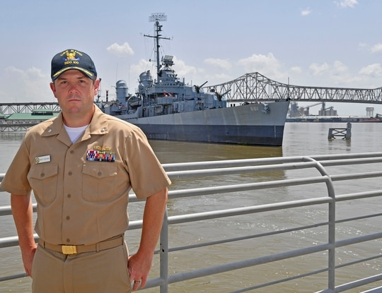 Cmdr. Matt Noland, who became the commanding officer of the current destroyer USS Kidd on May 12, 2021, stands before the original USS Kidd, on July 5, 2019, which served in World War II and is now the centerpiece of a military museum in Baton Rouge, La. (Hilary Scheinuk/The Advocate via AP)