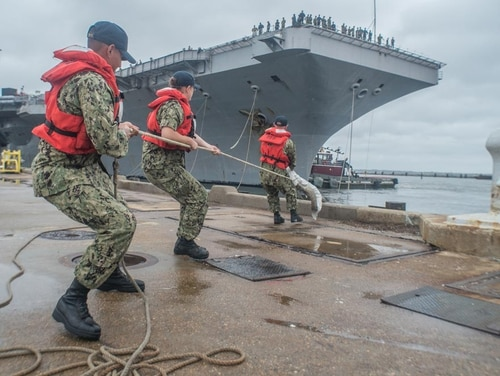 Sailors from the nearby aircraft carrier Abraham Lincoln pull on lines from the aircraft carrier Harry S. Truman, which arrived back at Norfolk Naval Station, Va., July 21, 2018. (Mark D. Faram/Navy Times)