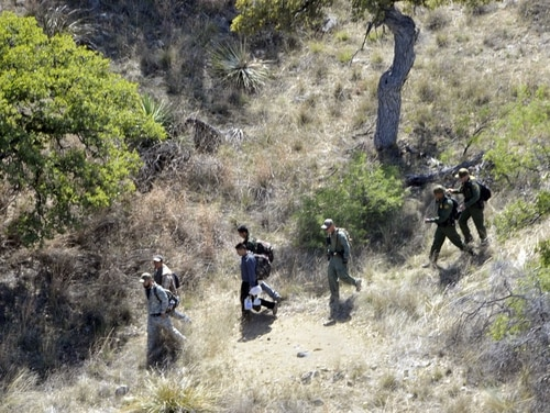 U.S. Border Patrol agents escort four undocumented immigrants captured near the U.S.-Mexico border on April 23, 2015. A Mississippi Army National Guard LUH-72 Lakota helicopter helped locate the men beneath a tree along a mountainside near Nogales, Ariz. (Staff Sgt. Scott Tynes/Army)