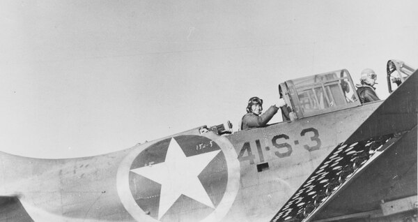 Photographer's Mate Second Class D. Mokos gestures as pilot Lt. C.V. Johnson prepares to take off on a photo-recon