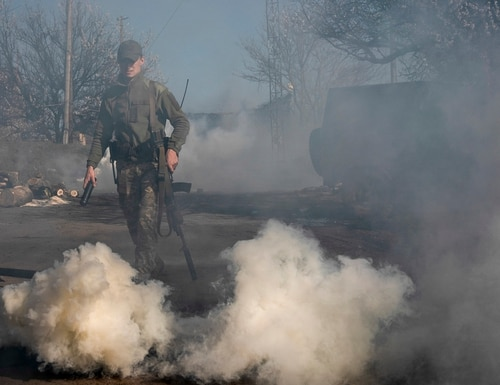 A Ukrainian serviceman makes smokescreen against military drones at a position near the front line in eastern Ukraine. (Evgeniy Maloletka/AP)