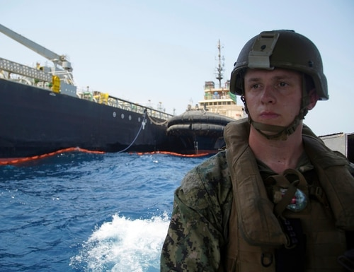 The damaged Panama-flagged, Japanese owned oil tanker Kokuka Courageous, that the U.S. Navy says was damaged by a limpet mine, is seen behind a U.S. sailor during a trip organized by the Navy for journalists, off Fujairah, United Arab Emirates, Wednesday, June 19, 2019. (Fay Abuelgasim/AP)