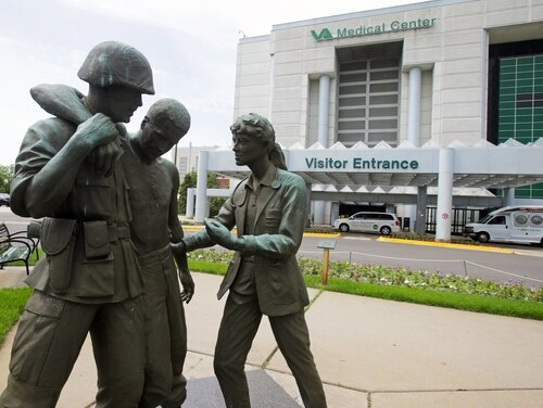 Three statues portraying a wounded soldier being helped, stand on the grounds of the Minneapolis VA Hospital in June 2014. (Jim Mone/AP)