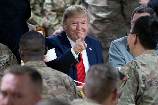 President Donald Trump points while eating during a surprise Thanksgiving Day visit to the troops, Thursday, Nov. 28, 2019, at Bagram Air Field, Afghanistan. (Alex Brandon/AP)