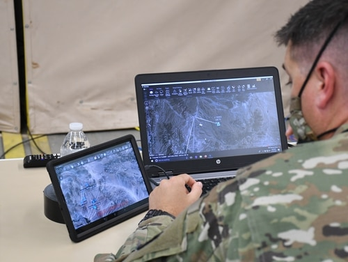A solider monitors air and ground position location information on the Windows Tactical Assault Kit (WINTAK) and Android Tactical Assault Kit (ATAK) to get a common operating picture that enhances situational awareness and data sharing at Project Convergence 2020. (Justine Ruggio/U.S. Army)