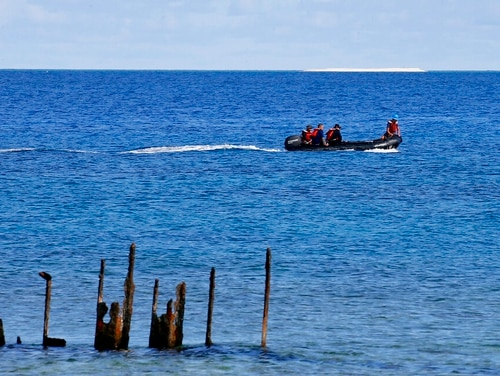 In this 2017 photo, engineers from NAMRIA, the central mapping agency of the Philippine Government, survey the area around the Philippine-claimed Thitu Island with a sandbar sitting on the horizon off the disputed South China Sea in western Philippines. (Bullit Marquez/AP)