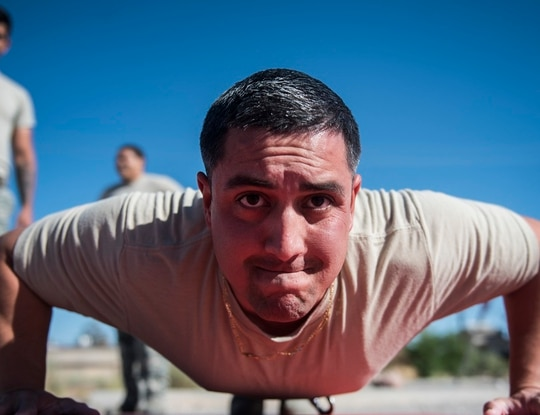Staff Sgt. Gabriel Cuevas, a K-9 handler assigned to the 99th Security Forces Squadron, does a push-up during the first stage of the Combat Fitness Challenge National Police Week event at Nellis Air Force Base, Nevada, in May 2018. The Air Force is extending its coronavirus-driven suspension of PT testing, which had been expected to resume in October. It will now resume in January. (Senior Airman Kevin Tanenbaum/Air Force)