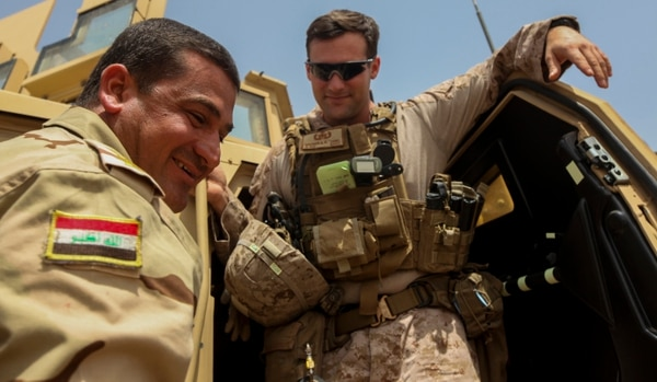 U.S. Marine Staff Sergeant Brewer, an explosive ordnance disposal technician attached to Task Force Al Asad, converses with an Iraqi EOD officer about the EOD program at Al Asad Air Base, Iraq, April 20, 2015. Task Force Al Asad is a coalition unit participating in Combined Joint Task Force – Operation Inherent Resolve's Building Partner Capacity mission, which trains and enables Iraqi Security Forces in their fight against the Islamic State of Iraq and the Levant by focusing on small unit leadership, medical procedures, air-ground integration, and equipping and sustainment processes. (U.S. Marine Corps Photo by Cpl. Cansin P. Hardyegritag)