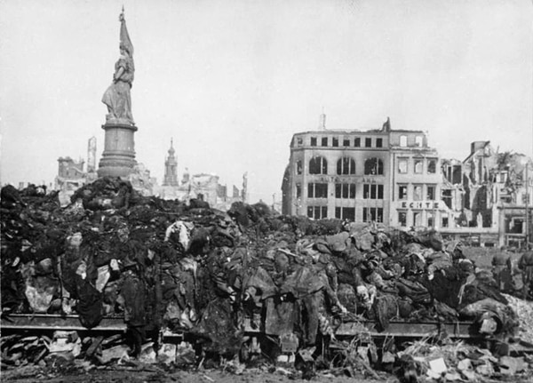 Piles of corpses in front of destroyed buildings in Dresden after air raids on Feb. 13 and 14, 1945. (Deutsches Bundesarchiv/Wikimedia Commons)