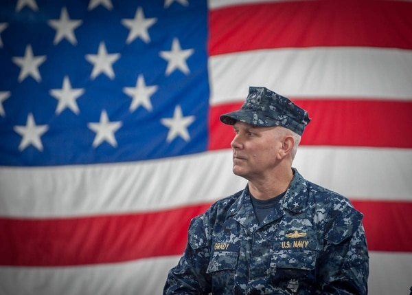 Then-Rear Adm. Christopher Grady waits to address the crew after taking command of Carrier Strike Group 1 during a ceremony aboard the aircraft carrier Carl Vinson off Southern California. (Petty officer 2nd Class George M. Bell/Navy)