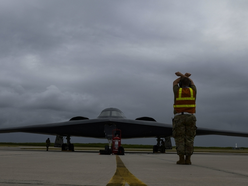 Staff Sgt. Mark Farrar, a crew chief from the 131st Aircraft Maintenance Squadron stationed at Whiteman Air Force Base, Missouri, marshalls a B-2 Spirit Stealth Bomber as it arrives at Naval Support Facility Diego Garcia, Aug. 12, 2020. (Tech. Sgt. Heather Salazar/Air Force)
