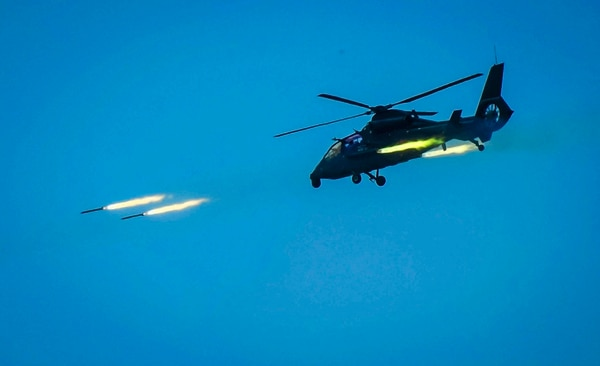 In this April 18, 2018, file photo released by China's Xinhua News Agency, an armed Chinese helicopter assaults targets with rocket projectiles in a live-fire exercise off China's southeast coast. (Li Shilong/Xinhua via AP)