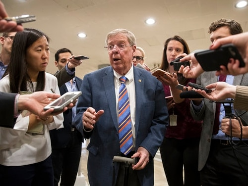 Sen. Johnny Isakson takes questions from reporters as he and other lawmakers head to the Senate floor for votes on Nov. 27, 2017. (J. Scott Applewhite/AP Photo)