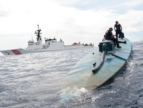 A boarding team from the U.S. Coast Guard Cutter Stratton investigates a self-propelled, semi-submersible in international waters off the coast of Central America in July 2015. (Petty Officer 2nd Class LaNola Stone/Coast Guard)