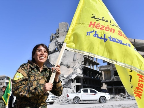 Rojda Felat, a Syrian Democratic Forces (SDF) commander, walks with her group's flag at the iconic Al-Naim square in Raqqa on Oct. 17, 2017. (Bulent Kilic/AFP/Getty Images)