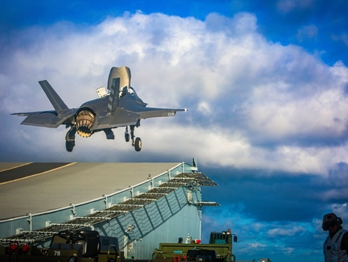 A Marine with Marine Fighter Attack Squadron (VMFA) 211 launches an F-35B Lightning II Joint Strike Fighter from the deck aboard Her Majesty's Ship (HMS) Queen Elizabeth at sea on Oct. 10, 2020. (1st Lt. Zachary Bodner/Marine Corps)
