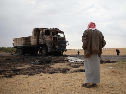 A Syrian man looks at a destroyed truck at the spot where Abu Hassan al-Muhajir, the Islamic State group's spokesman, was reportedly killed in an Oct. 28 raid in the northern Syrian village of Ayn al-Bayda near Jarablus. (Aaref Watad/AFP via Getty Images)