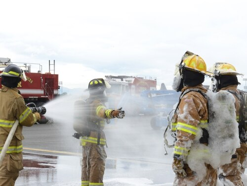 Firefighters from the 673d Civil Engineer Squadron rinse off foam after a hangar test on Joint Base Elmendorf-Richardson in Alaska on Aug. 31, 2017. Lawmakers are considering banning use of the foam in most base training activities because of worries over toxic exposures. (Airman 1st Class Caitlin Russell/Air Force)