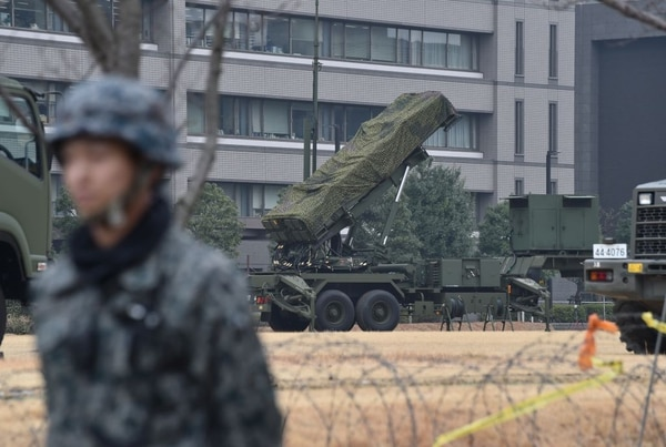 A Japan Self-Defense Forces soldier stands guard near a PAC-3 surface-to-air missile launcher unit (C), used to engage incoming ballistic missile threats, in position at the Defence Ministry in Tokyo on March 6, 2017. Three of the four missiles North Korea launched March 6 landed in Japanese-controlled waters, Prime Minister Shinzo Abe said, calling the development a