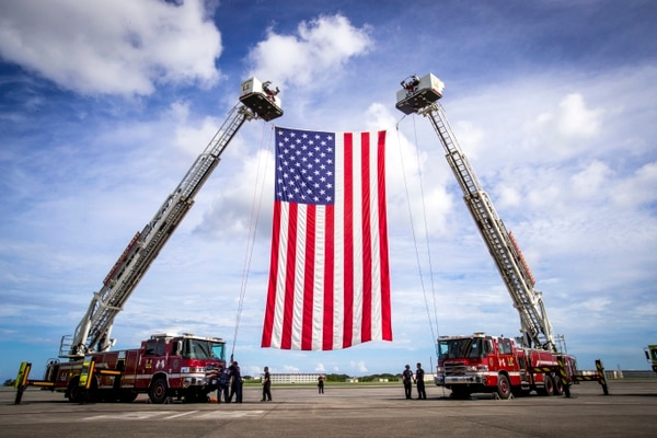 Personnel with Fire and Emergency Services, Marine Corps Installations Pacific - Marine Corps Base Camp Butler, hoist the American flag on Marine Corps Air Station Futenma on Thursday. They were prepping for a change of command ceremony, with Maj. Gen Paul Rock Jr. scheduled to relinquish his post as Commanding General of Marine Corps Installations Pacific to U.S. Marine Corps Brig. Gen. William J. Bowers on Friday. (Lance Cpl. Savannah Mesimer/Marine Corps)