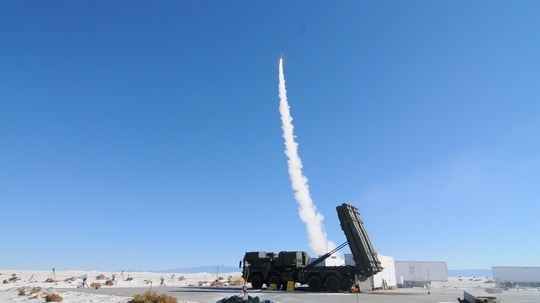 A MEADS launcher sits ready while a second fires a missile in the background at White Sands Missile Range, N.M., in 2013. (White Sands Missile Range Public Affairs)