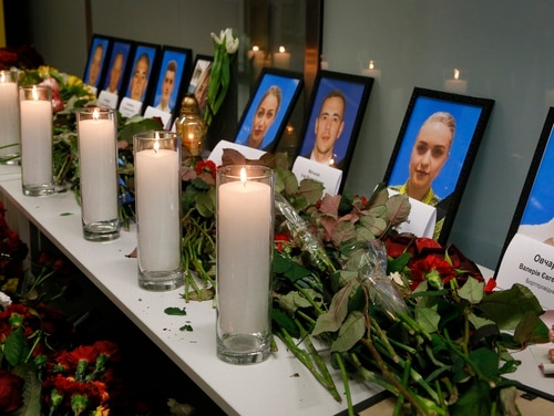 Flowers and candles are placed in front of portraits of the flight crew members of the Ukrainian 737-800 plane that crashed on the outskirts of Tehran, at a memorial inside Borispil international airport outside Kyiv, Ukraine, on Wednesday. A Ukrainian airplane carrying 176 people crashed on Wednesday shortly after takeoff from Tehran's main airport, killing all on board. (Efrem Lukatsky/AP)