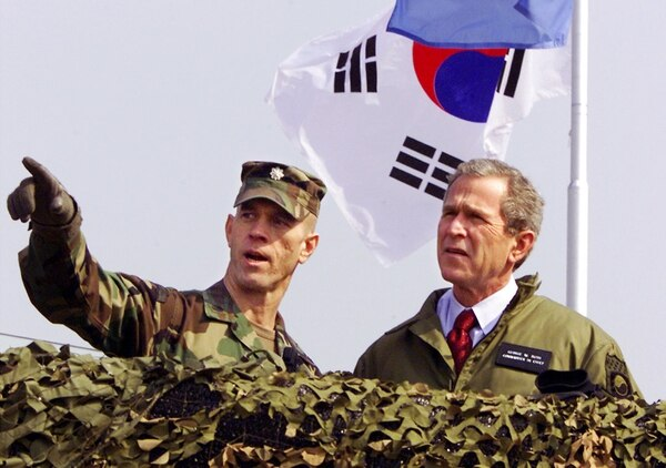 In this Feb. 20, 2002, file photo, then-U.S. President George W. Bush, right, gazes out at North Korea from Observation Point Ouellette in the Demilitarized Zone, the tense military border between the two Koreas, in Panmunjom, South Korea. Bush visited the DMZ a few weeks after he labeled North Korea part of an